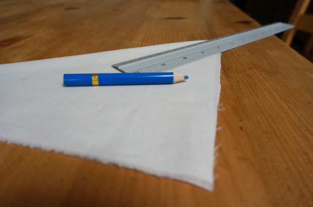 Start with a square of folded fabric, ruler and marking tool